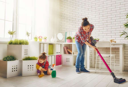 Photo for Happy family cleans the room. Mother and daughter do the cleaning in the house. A young woman and a little child girl wiped the dust and vacuumed the floor. - Royalty Free Image