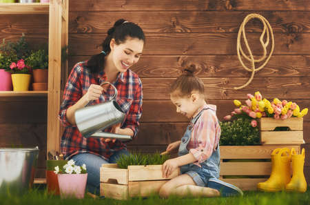 Foto de Cute child girl helps her mother to care for plants. Mother and her daughter engaged in gardening in the backyard. Spring concept, nature and care. - Imagen libre de derechos