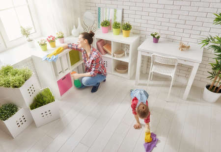 Photo pour Happy family cleans the room. Mother and daughter do the cleaning in the house. A young woman and a little child girl dusting. - image libre de droit