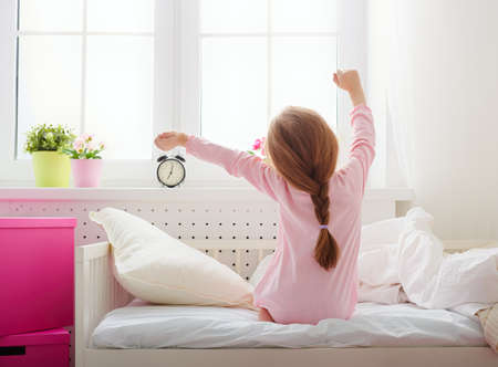 Photo for A nice child girl enjoys sunny morning. Good morning at home. Child girl wakes up from sleep. - Royalty Free Image