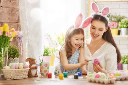 Photo pour Happy easter! A mother and her daughter painting Easter eggs. Happy family preparing for Easter. Cute little child girl wearing bunny ears on Easter day. - image libre de droit