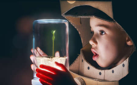 Foto de Child is dressed in an astronaut costume. Child sees a sprout in a glass case. The concept of environmental protection. - Imagen libre de derechos