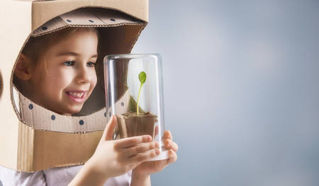 Photo for Child is dressed in an astronaut costume. Child sees a sprout in a glass case. The concept of environmental protection. - Royalty Free Image