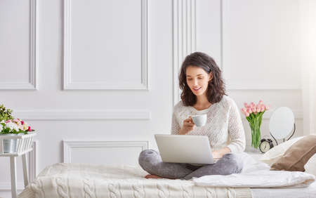 Photo pour Happy casual beautiful woman working on a laptop sitting on the bed in the house. - image libre de droit