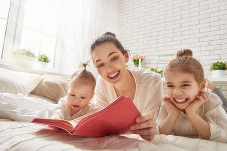 Foto de happy loving family. pretty young mother reading a book to her daughters - Imagen libre de derechos