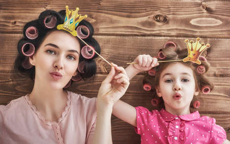 Photo pour Funny family! Mother and her child daughter girl with a paper accessories. Beauty funny girl holding paper crown on stick. Beautiful young woman holding paper crown on stick. - image libre de droit