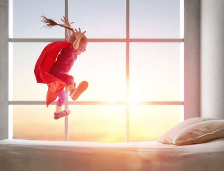 Foto de Child girl in Superhero's costume plays. The child having fun and jumping on the bed. - Imagen libre de derechos