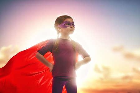 Foto de Little child girl plays superhero. Child on the background of sunset sky. Girl power concept - Imagen libre de derechos