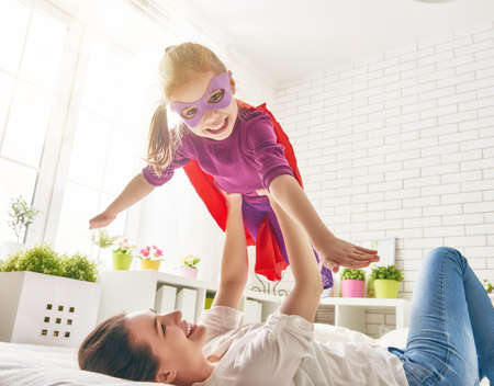 Photo for Mother and her child girl playing together. Girl in an Superhero's costume. The child having fun and jumping on the bed. - Royalty Free Image