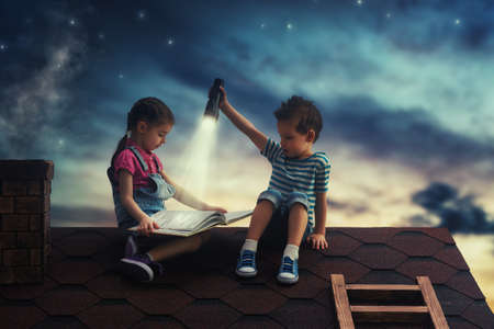 Photo pour Children reading a book sitting on the roof of the house. Boy and girl reading by the light of a flashlight at night. - image libre de droit
