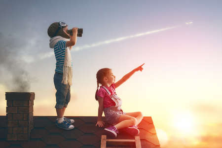 Photo pour Two little children playing on the roof of the house and looking at the sky and dreaming of becoming a pilots. - image libre de droit
