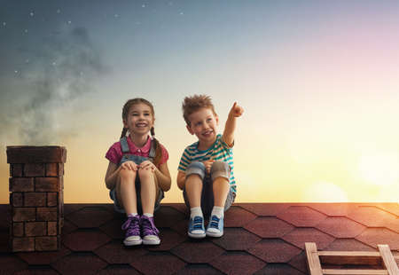 Photo for Two cute children sit on the roof and look at the stars. Boy and girl make a wish by seeing a shooting star. - Royalty Free Image