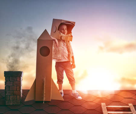 Photo for Little child boy plays astronaut. Child on the background of sunset sky. Child boy in an astronaut costume standing on the roof of the house and looking at the sky and dreaming of becoming a spaceman. - Royalty Free Image