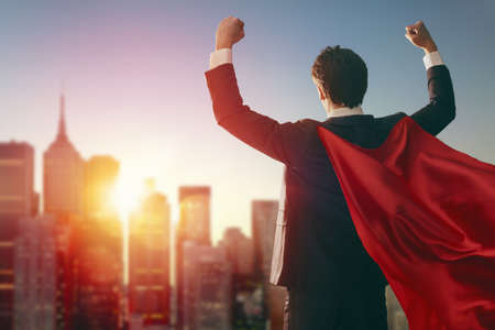 Photo pour superhero businessman looking at city skyline at sunset. the concept of success, leadership and victory in business. - image libre de droit