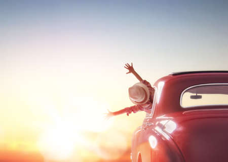 Photo pour Toward adventure! Girl relaxing and enjoying road trip. Happy girl rides into the sunset in vintage car. - image libre de droit