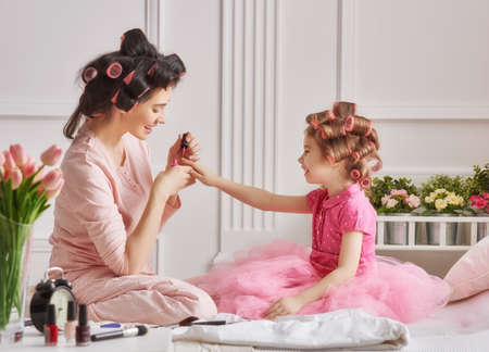 Photo for Happy loving family. Mother and daughter are doing hair, manicures and having fun. Mother and daughter sitting on the bed in the bedroom. - Royalty Free Image