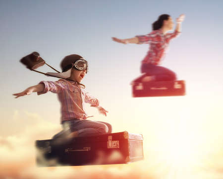 Foto de Dreams of travel! Child girl and her mom flying on a suitcase against the backdrop of a sunset. - Imagen libre de derechos