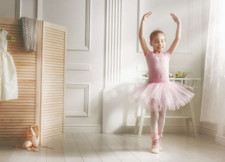 Foto de Cute little girl dreams of becoming a ballerina. Child girl in a pink tutu dancing in a room. Baby girl is studying ballet. - Imagen libre de derechos