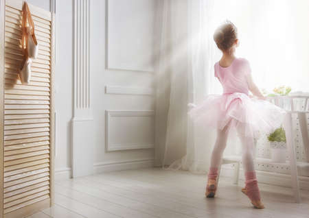 Photo for Cute little girl dreams of becoming a ballerina. Child girl in a pink tutu dancing in a room. Baby girl is studying ballet. - Royalty Free Image