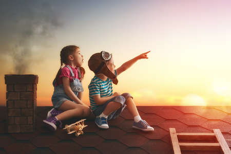 Foto de Two little children playing on the roof of the house and looking at the sky and dreaming of becoming a pilots. - Imagen libre de derechos
