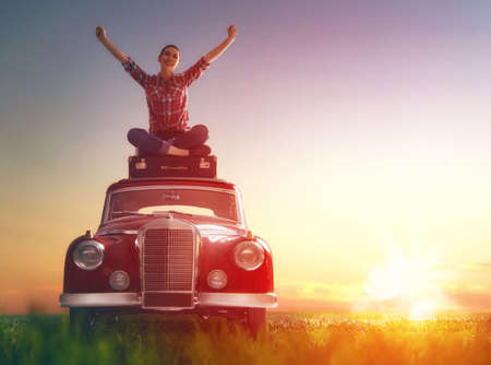 Photo pour Toward adventure! Girl relaxing and enjoying road trip. Beautiful young woman sitting on roof of vintage car. - image libre de droit