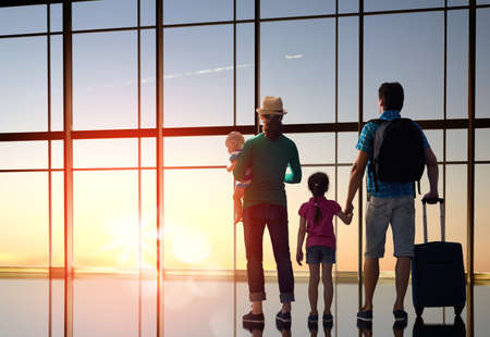 Photo pour Happy family with children at the airport. Parents and their children look out the window at the plane. - image libre de droit