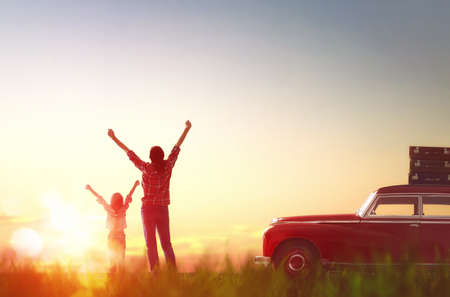 Toward adventure! Happy family relaxing and enjoying road trip. Beautiful young mother and her child girl rejoice in the dawn.