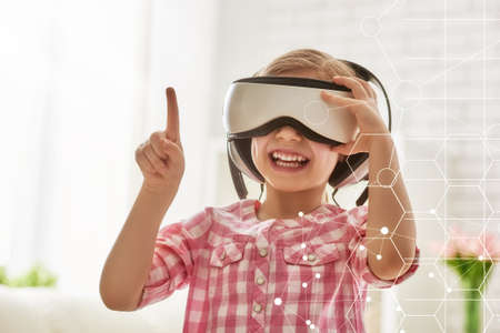 Photo pour Cute little child girl playing game in virtual reality glasses. - image libre de droit