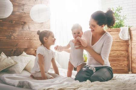 Foto de Happy loving family. Mother and her daughters children girls playing and hugging. - Imagen libre de derechos