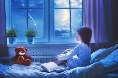 Foto de Cute child girl sitting at the window and looking at the stars. Girl making a wish by seeing a shooting star at bedtime night. - Imagen libre de derechos