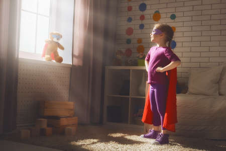 Foto de Little child girl plays superhero. Child plays with her friend a Teddy bear. Girl power concept. - Imagen libre de derechos