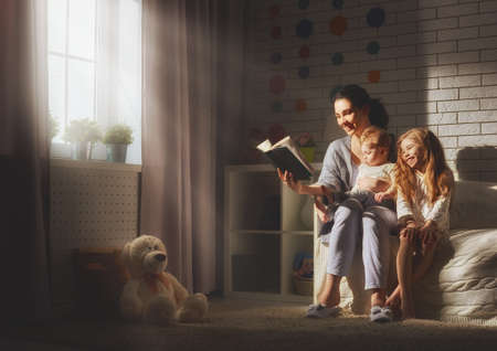 Family reading bedtime. Pretty young mother reading a book to her daughters.