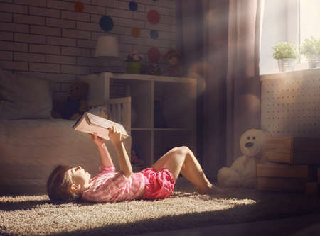 Foto de Cute little child girl reading a book. - Imagen libre de derechos