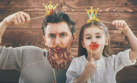 Photo for Funny family! Father and his child daughter girl with a paper accessories. Beauty funny girl holding paper lips and crown on stick. Beautiful young man holding paper beard and crown on stick. - Royalty Free Image