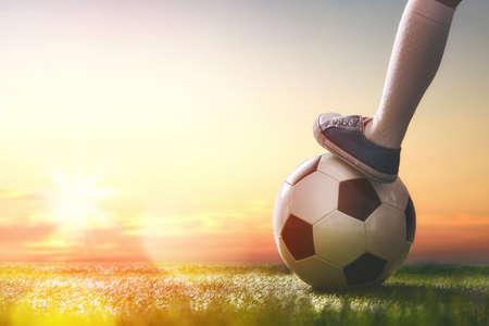 Foto de Cute little child dreams of becoming a soccer player. Child plays football. - Imagen libre de derechos