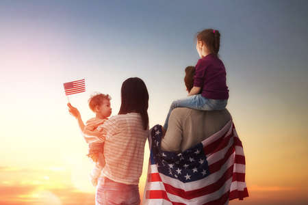Photo pour Patriotic holiday. Happy family, parents and daughters children girls with American flag outdoors. USA celebrate 4th of July. - image libre de droit