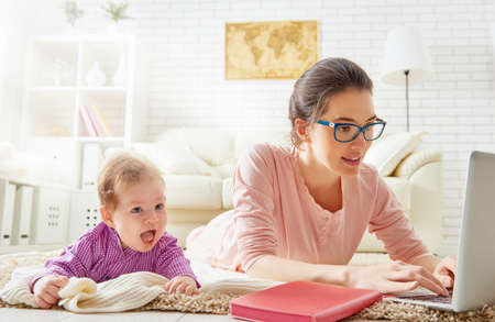 Photo for happy family. mom and baby. a young mother working with laptop at home - Royalty Free Image