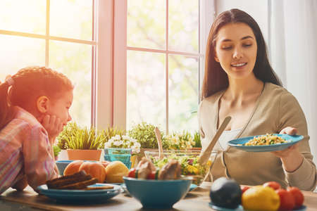 Photo pour Happy family having dinner together sitting at the rustic wooden table. Mother and her daughter enjoying family dinner together. - image libre de droit