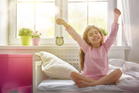 Photo pour A nice child girl enjoys sunny morning. Good morning at home. Child girl wakes up from sleep. - image libre de droit