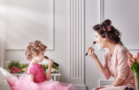 Photo for Happy loving family. Mother and daughter are doing hair and having fun. Mom and child doing your makeup sitting on the bed in the bedroom. - Royalty Free Image