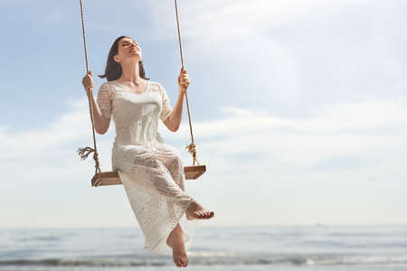 Photo pour beautiful young woman on a swing on summer day outdoors - image libre de droit