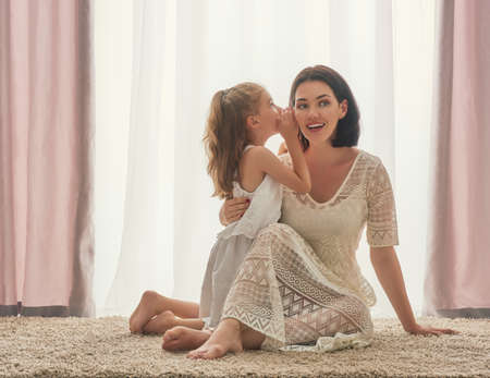Photo for Happy loving family. Mother and her daughter child girl playing and hugging. Daughter whispering to mom a secret. - Royalty Free Image