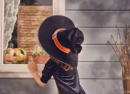 Photo for Happy Halloween! Cute cheerful little witch outdoors. Beautiful child girl in witch costume near house decorated to Halloween. - Royalty Free Image