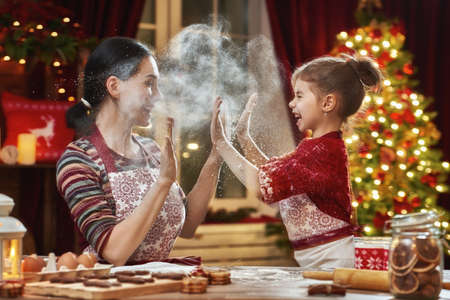 Photo pour Merry Christmas and Happy Holidays. Family preparation holiday food. Mother and daughter cooking Christmas cookies. - image libre de droit
