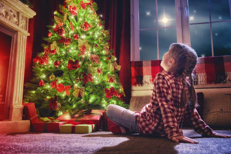 Merry Christmas and Happy Holidays! Cute little child girl looking at decorations the Christmas tree. Christmas family traditions.