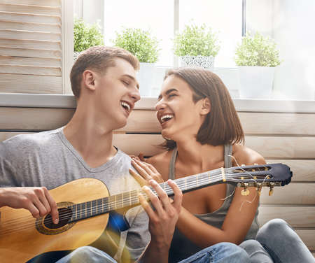 Photo pour Happy couple in love. Stunning sensual portrait of young stylish fashion couple indoors. Young man playing guitar for his beloved girl. - image libre de droit