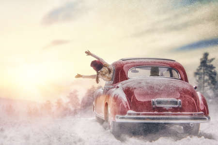 Toward adventure! Happy family relaxing and enjoying road trip. Parent, child and vintage car on snowy winter nature background. Christmas holidays time.