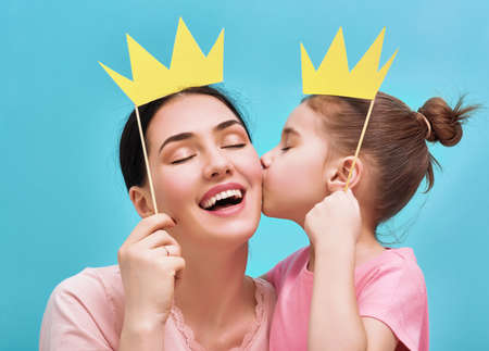 Photo pour Funny family on a background of bright blue wall. Mother and her daughter girl with a paper accessories. Mom and child are holding paper crown on stick. - image libre de droit