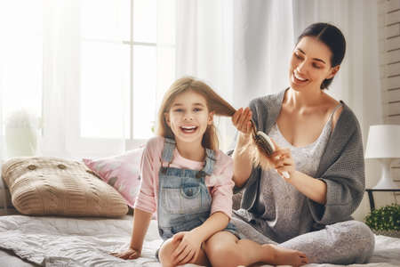 Photo for Happy loving family. Mother is combing her daughter's hair sitting on the bed in the room. - Royalty Free Image