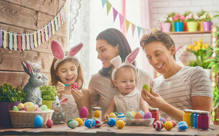 Photo pour Mother, father and daughters are painting eggs. Happy family are preparing for Easter. Cute little child girl wearing bunny ears. - image libre de droit